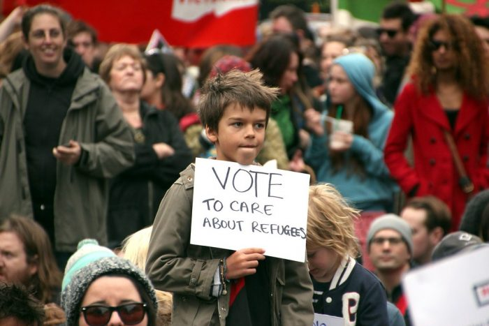 "Child holds sign telling Melbourne, Australia to ""vote to care about refugees"""