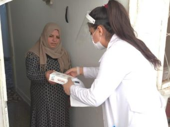 Syrian refugee woman receiving donation