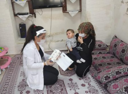 Syrian refugee woman and her child receive donated personal protective equipment and covid-19 training