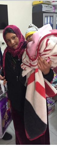 Syrian refugee woman with child in her arms picks up basic humanitarian supllies